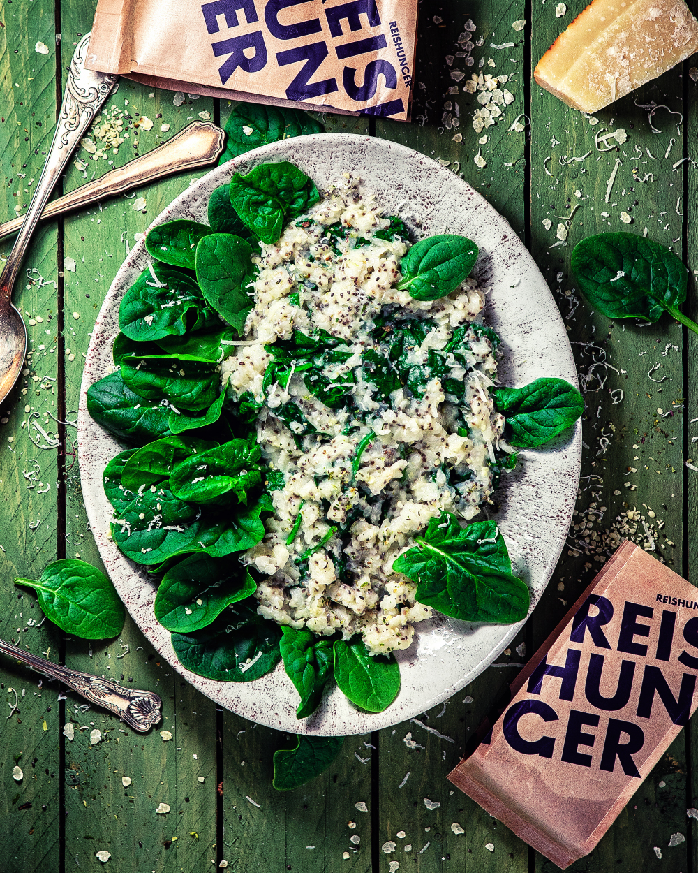 Parmesan Spinat Porige auf Steinteller vor grünem Hintergrund